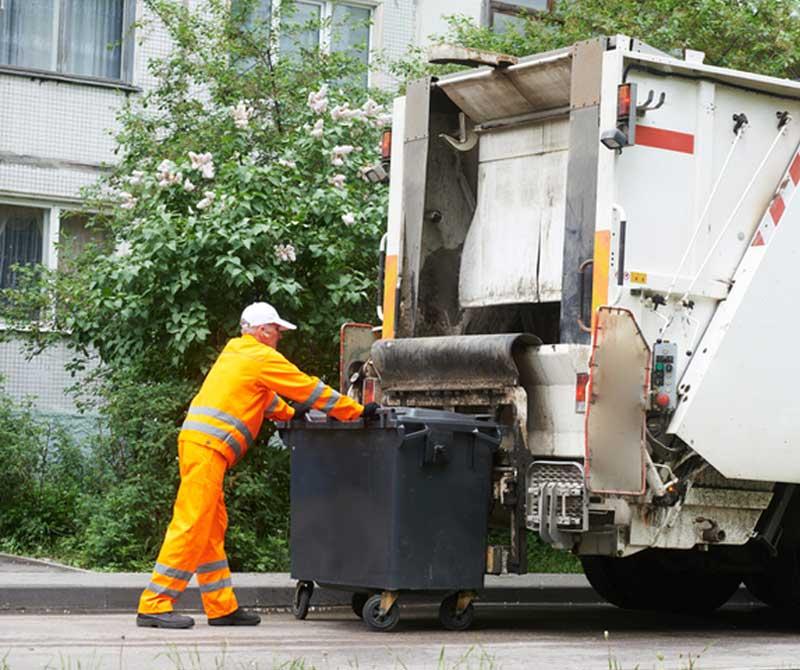 man emptying a dust bin into a truck